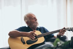 The old man and his guitar in the house