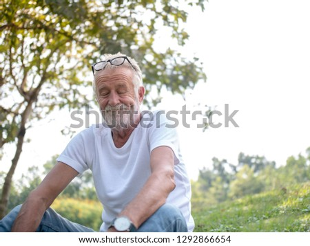 The old man is relaxing in the park with a smile, good mood, good health, close his eyes.