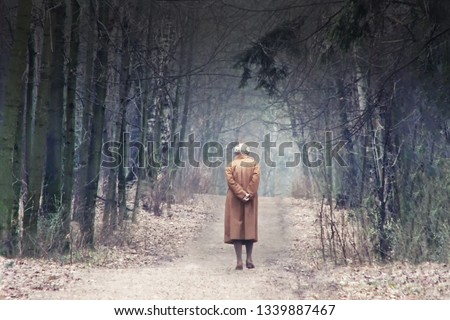 The old man leaves the road among the trees. Abstract aging, people of retirement age, passing time, lived life. The youth does not return. Loneliness and near death. Soon end of life. #1339887467
