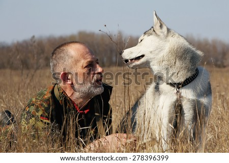 The old man playing with his dog. Man and dog in the hunt. Siberian husky.