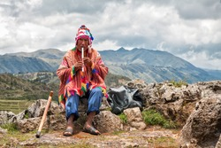 The old man Quechua dressed in a colored poncho and a cap of Chullo, sits on the rocks with a view of the mountains in the background and plays on the musical instrument of Quena. Cusco, Peru.