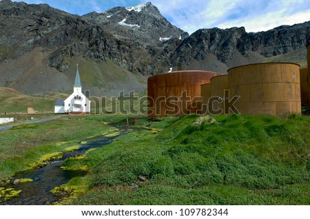 The old Norwegian church at the former whaling station of Grytviken in South Georgia with whale oil storage tanks in the foreground