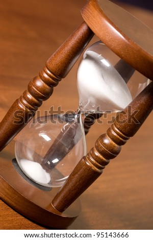 The old ourglasses on a wooden table