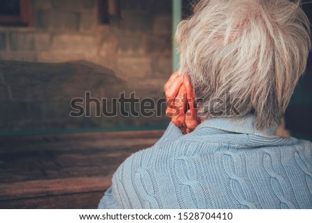The old person was sad and stressed. He sitting put hand prop up on the chin in the darkroom. Concept: dementia, dramatic loneliness, sadness, depression, disappointed, abuse, healthcare, and pain.