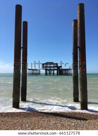 The old pier at Brighton old architecture now derelict with waves crashing on supports #661127578
