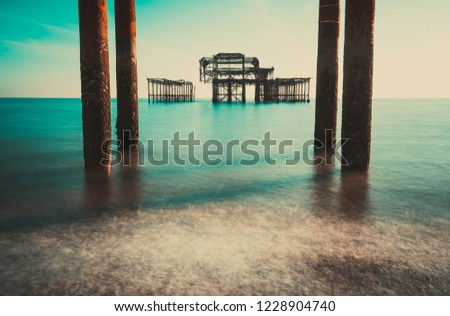 The old remains of Brighton Pier left standing in sea with beautiful waves in Brighton and Hove's West Pier. Old vintage West Pier Brighton Beach.