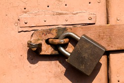 the old rusting metal lock on which the old door is closed is covered with metal and painted with orange paints, the property protection system with a padlock