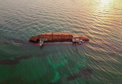 The old rusty ship was stranded by a storm. Oil spill from a tanker, environmental pollution. Ship at sunrise