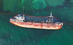 The old rusty ship was stranded by a storm. Oil spill from a tanker, environmental pollution. Top view of a rusty ship in the sea.