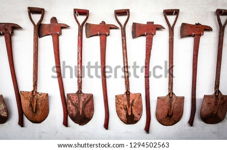 The old set of tools,shovel and ax is hanging on the old white wall background