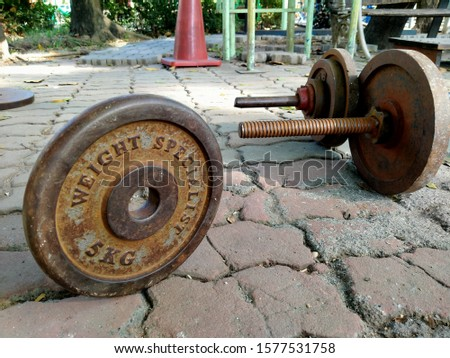 The old steel plates and barbells for lifting weights on the floor.