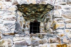 The old stone castle defensive wall. Prison window, justice in the old days.