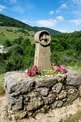 The old stone sign in the beautiful mountain valley in Pyrenees shows the way to the last cathar fortress Montsegur in the south of France