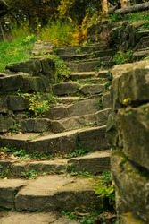 The old stone steps on a hill with grass growing on both sides. Stone stairs up a grass hill.