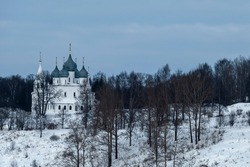 The old stone temple of the city of Tutaev on the bank of the Volga River. Holy Cross Cathedral is an example of local architecture of the mid-XVII century. White temple with blue domes in winter