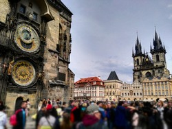 The Old Town Square in Prague crowded with tourists. On the left is the Prague Astronomical Clock and there is the Church of Our Lady before Týn on the right side hidden behind other buildings