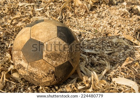 the old used football or soccer ball on the messy ground