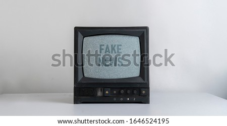 the old vintage tv with gray noise on screen with fake news text overlay, standing on shelf at home
