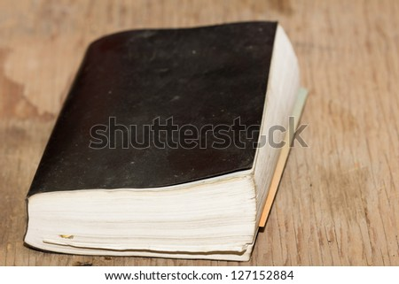 The old, wise book lies on a wooden background