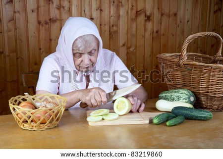 The old woman cuts  vegetable marrow on a table