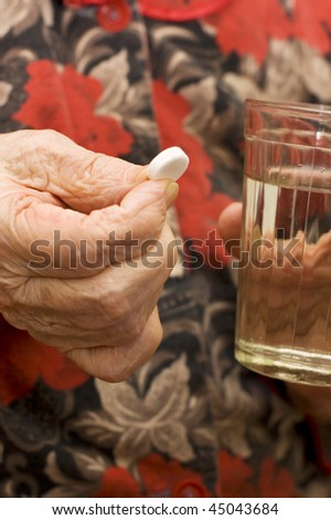 The old woman drinks a tablet