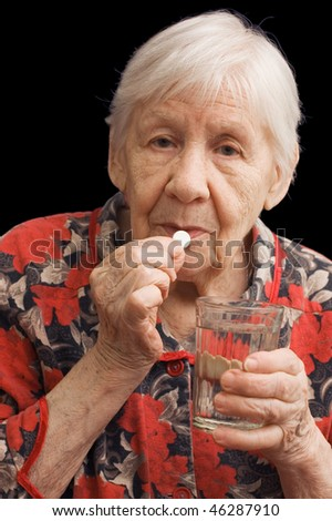 The old woman drinks a tablet - stock photo