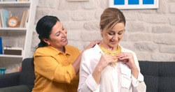 The old woman gives a golden necklace to her adult daughter as a gift. The woman wears the gold necklace she gave as a gift to her daughter's neck.