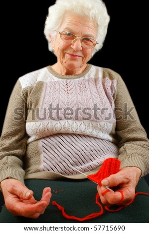 The old woman is engaged in knitting on a black background
