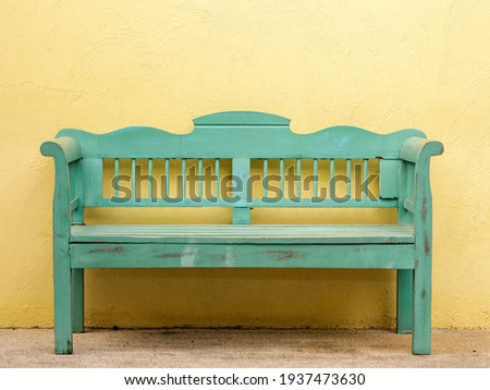 The old wooden bench in green color in front of the yellow wall. Wooden 2 seater garden bench. The green wooden bench and the yellow wall. Garden or outdoor furniture. Сток-фото ©