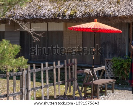 the old wooden bench with big red umbrella and old wooden fence in front of the vintage house