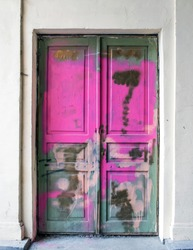 The old wooden door is stained and painted with graffiti and bright colors. An old abandoned building in the historical center of Lviv. Industrial abandoned grunge background.