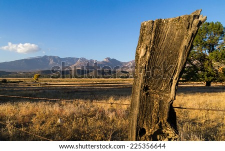 The old wooden fence post in the country before sunset.