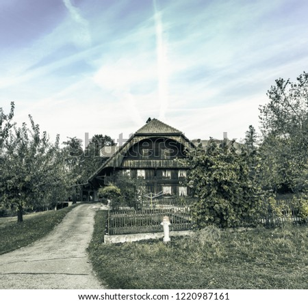 The old wooden house with a fence surrounding,picture vintage dark tone.