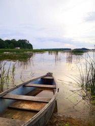 The oldest artificial lake in Lithuania at sunset with and a wooden boat