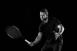 The one caucasian man playing tennis isolated on black background. Studio monochrome shot of fit young player at studio in motion or movement during sport game..