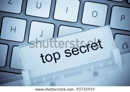 the one hanging folder tab before a computer keyboard on top secret