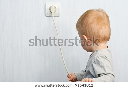 The one-year-old child pulls for an electric wire