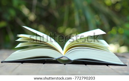 the open book on the wooden table with the blur nature background, in concept of education, textbook, academic, learning, student, university, research #772790203