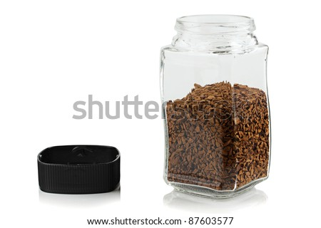 The open glass jar of instant coffee.