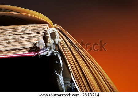 The opened old book on an orange background