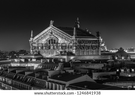 The Opera of Paris at night in black and white with dramatic tonality, light and shadows. High-resolution pic from long exposure. Surrounding buildings are part of the image showing the Paris skyline.
