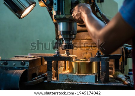 The operation of NC milling machine by technician operator. The shop floor operation by NC milling machine. Сток-фото ©