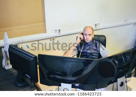 The operator is talking on the phone. The system administrator sits in front of several monitors. Department of customer support and monitoring. The man works on computers #1186423723