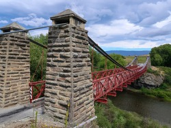 The Ophir suspension bridge is a classic one-way red bridge built during the Central Otago Gold Rush, South Island, New Zealand