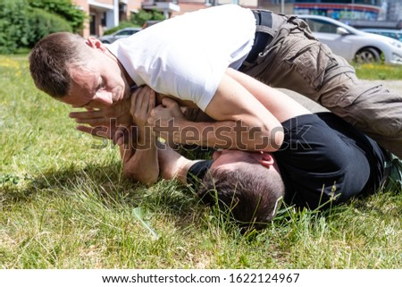The opponent uses the technique to immobilize the attacker. Close-up. Martial arts instructors demonstrate self-defense techniques of Krav Maga