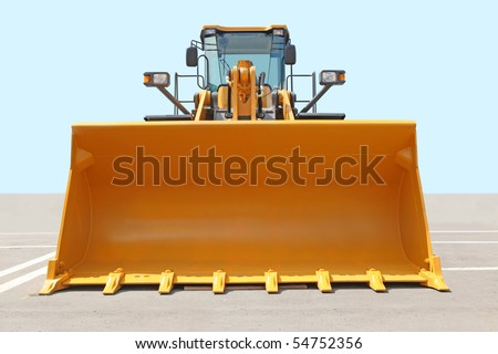 The orange bulldozer on a concrete platform against the sky