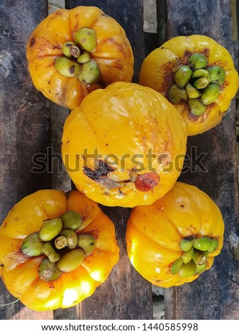 The orange fruit is called Garcinia. It is used in cooking with sour taste.