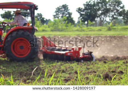 The orange tractor is plowing for farming in the farming season, taking a blurred image