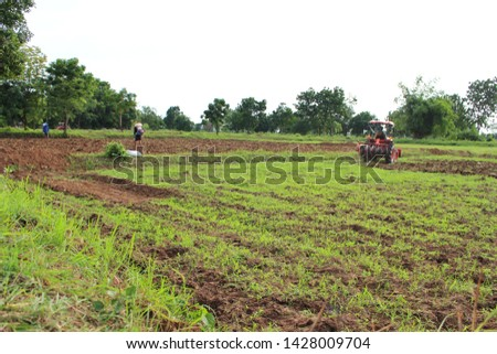The orange tractor is plowing for farming in the farming season, taking a blurred image #1428009704