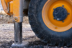 The orange Wheels covered in mud tractor. Agronomy, farming concept. Agriculture. Close up of a large yellow wheel of a tractor with black tire, agricultural machinery. Hydraulic foot of the crane.